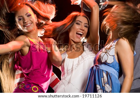 Photo of joyful teenage girls having fun on dance floor - stock photo