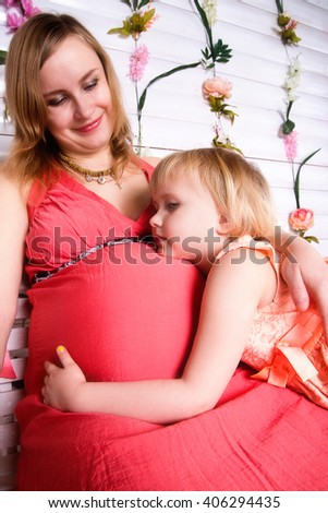 photo of kid girl hugging pregnant mother's belly - stock photo