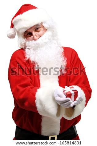 Photo of kind Santa Claus giving xmas present and looking at camera  - stock photo
