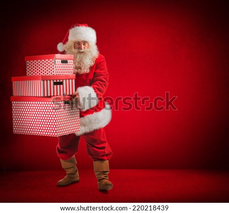 Photo of kind Santa Claus holding huge gift boxes and looking at camera. Full length portrait - stock photo