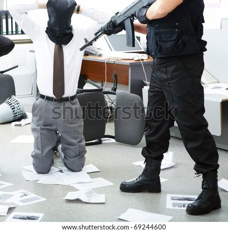 Photo of kneeling businessman wearing black sacks on head with burglar standing near by - stock photo