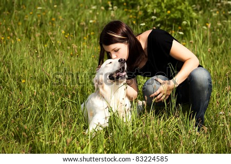 Photo of lady kissing her lovely dog in the open air