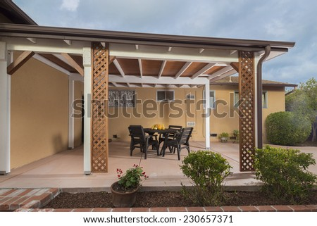 Photo of large cedar deck with patio furniture and trees in background. - stock photo