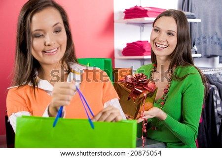 Photo of laughing woman at background laughing and looking at her friend in trade center - stock photo