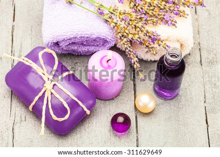 Photo of lavender soap, essential oil and bath pearls over wooden table - stock photo