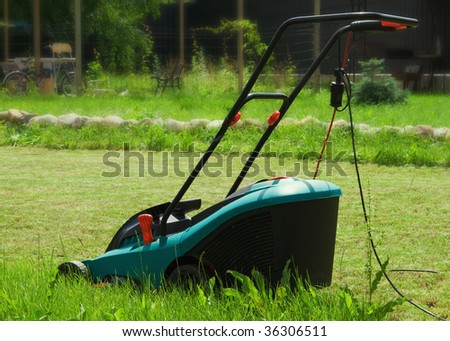 Photo of lawn mower and green lawn