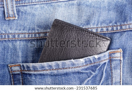 Photo of leather wallet in jeans back pocket. - stock photo