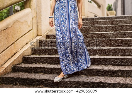 Photo of legs of a girl who comes down the stairs. Girl with long dress. - stock photo