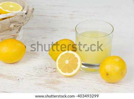 Photo of lemons and juice in a glass on white wooden board