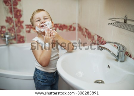 photo of little boy playing with shaving foam - stock photo