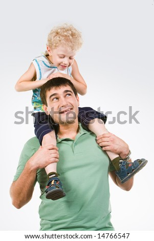 Photo of little boy sitting on fatherâ??s neck looking at his eyes - stock photo