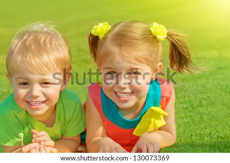 Photo of little brother and sister lying down on green grass field in sunny day, two adorable child playing on backyard, cute friends laughing outdoors in spring, preschooler kid, happy family concept - stock photo