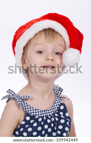 photo of little funny girl with santa hat