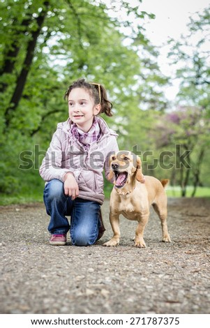 Photo of little girl with a dog - stock photo