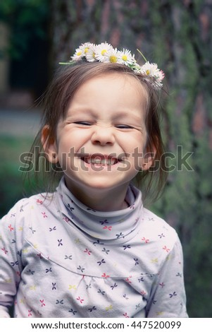 photo of little girl with a wreath of daisies on her head