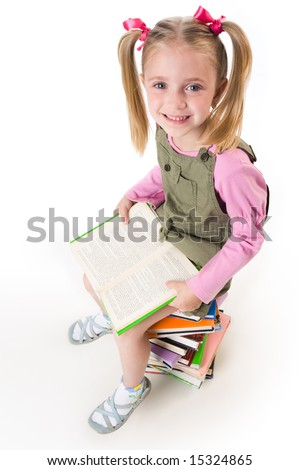 Photo of little girl with book in hands looking at camera happily - stock photo