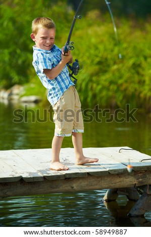 Photo of little kid pulling rod while fishing on weekend - stock photo