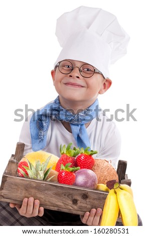 photo of little smiling Chef cook, pretty little boy in chef hat, young chef holding an old wooden crate with fruits, isolated over white background. Cooking concept.