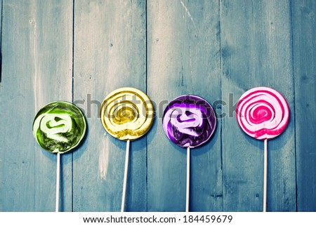 Photo of 4 lollipops on wooden - stock photo