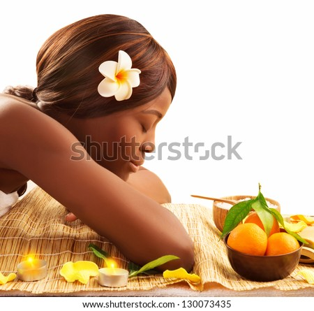 Photo of lovely African woman with closed eyes and white franjipani flower in head relaxed on massage table in luxury spa salon, enjoying dayspa, healthy lifestyle, beauty treatment, pampering concept - stock photo