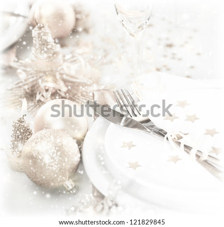 Photo of luxury festive table setting, beautiful white dishware decorated with silver baubles and candles, elegant plate served with knife and fork, Christmastime home interior, New Year dinner - stock photo