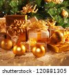 Photo of luxury gift boxes under Christmas tree, New Year home decorations, golden wrapping of Santa presents, festive fir tree decorated with garland, baubles and angels, traditional celebration - stock photo