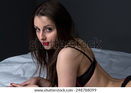 Photo of lying young brunette on gray background - stock photo