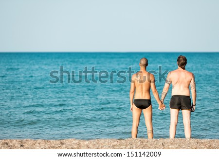 Photo of male couple holding hand at the beach - stock photo