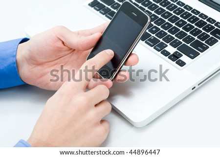 Photo of male hand holding cellular phone and touching its sensor screen - stock photo