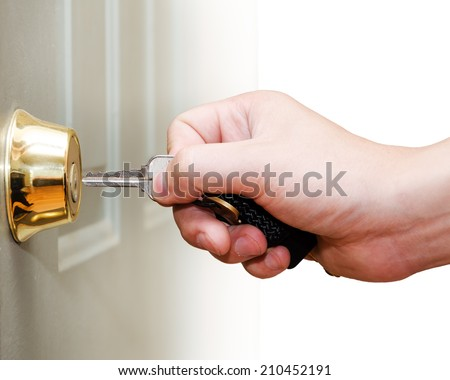 Photo of male hand putting house key into front door lock of house - stock photo