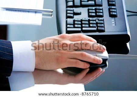 Photo of male hand using computer mouse lying on a workplace