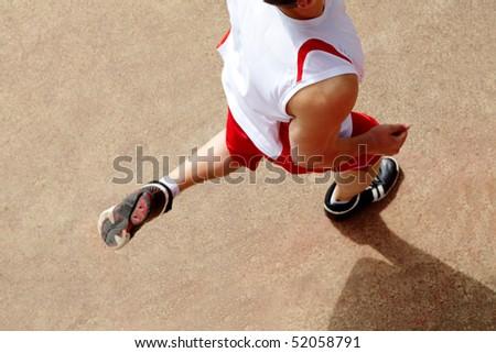 Photo of male in sportswear running down stadium track - stock photo