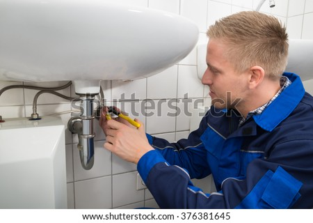 Photo Of Male Plumber Fixing Sink In Bathroom