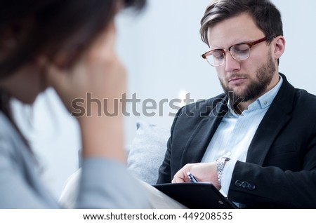 Photo of male psychologist in suit with patient during session - stock photo