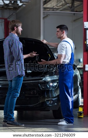 Photo of man and mechanic talking at workshop