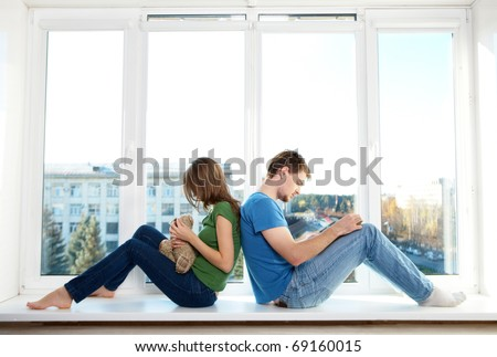 Photo of man and woman sitting back to back on the windowsill - stock photo