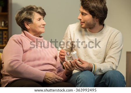 Photo of man helping his ill grandmother - stock photo