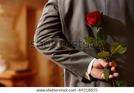 Photo of man in suit holding a red rose behind his back - stock photo