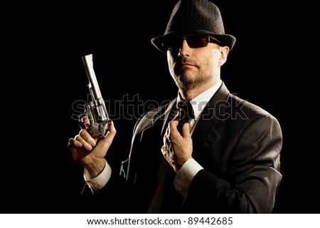 Photo of man shot with studio lighting, holding a handgun, with Fedora Hat, Dark Suit and Sun Glasses.