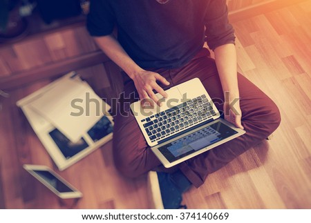 Photo of man sitting in studio and working on his laptop. Blurred background - stock photo
