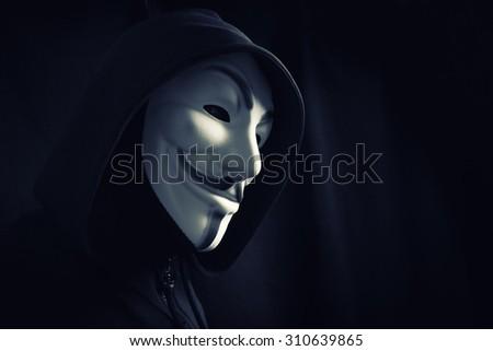 Photo of man wearing Vendetta mask,hooligan under hood - stock photo