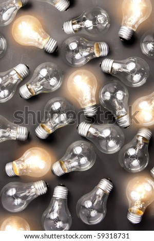photo of many light bulbs lying on black background - stock photo