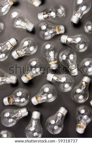 photo of many light bulbs lying on black background - stock photo
