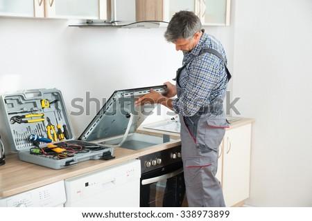 Photo Of mature repairman examining stove in kitchen - stock photo