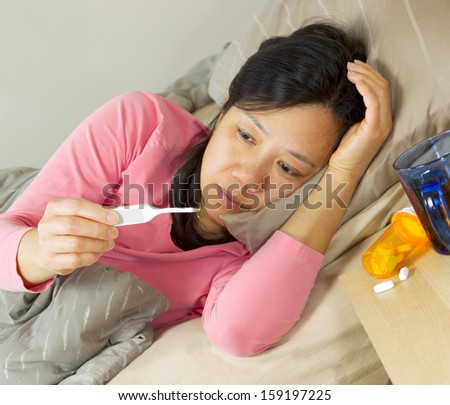 Photo of mature woman testing her temperature with focus on thermometer while lying in bed sick - stock photo