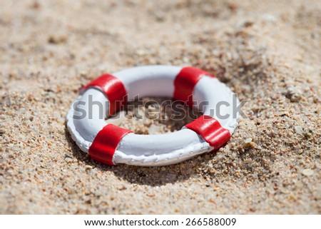 Photo Of Miniature Lifebuoy Lying On Sand - stock photo