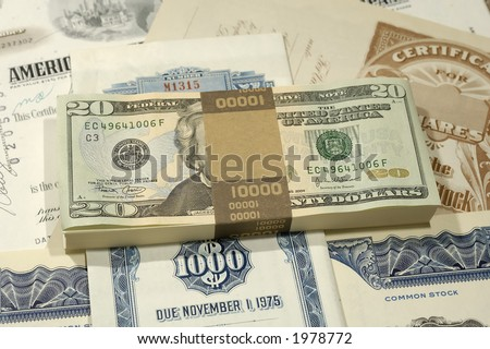 Photo of Money on Top of Stock Certificates - Investing Concept - stock photo