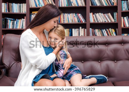 Photo of mother and little daughter. Nice cozy interior with big bookcase. Daughter looking at camera and smiling while mother kissing her - stock photo
