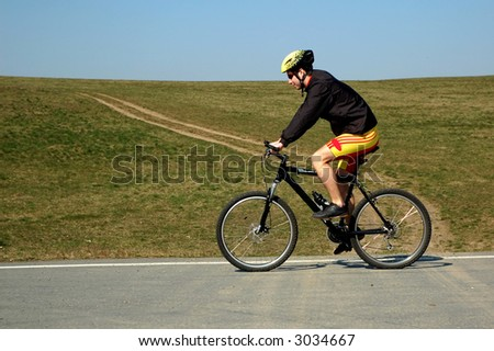Photo of mountain biker in sporting costume with helmet. - stock photo