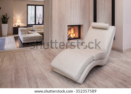 Photo of new design white leather armchair standing beside fireplace - stock photo